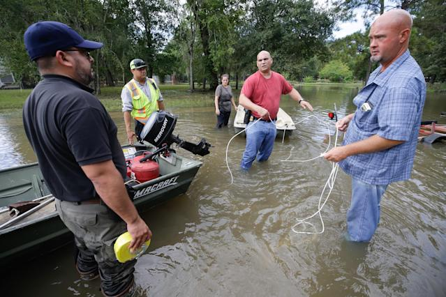 Robert Spooner, a U.S. Customs and Border Patrol officer, center, and other volunteers work to prepare boats to help people in the aftermath of Harvey, Wednesday in Houston. Harvey's floodwaters started dropping across much of the Houston area, but many thousands of homes in and around the nation's fourth-largest city were still swamped and could stay that way for days or longer. (Brett Coomer/Houston Chronicle via AP)