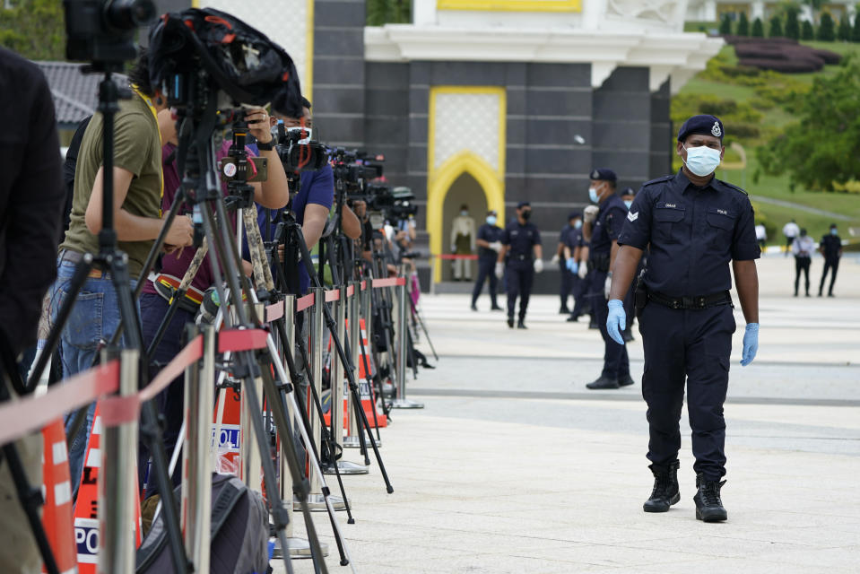 Police wearing a face mask to help curb the spread of the coronavirus guard media outside National Palace in Kuala Lumpur, Malaysia, Sunday, Oct. 25, 2020. Malay rulers hold a special meeting on Sunday to discuss the government's plan to declare an emergency to tackle the worsening COVID-19 situation. (AP Photo/Vincent Thian)