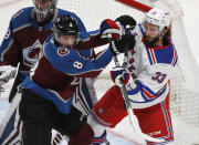 Colorado Avalanche defenseman Cale Makar, left, fights for position in front of the net with New York Rangers left wing Phillip Di Giuseppe during the first period of an NHL hockey game Wednesday, March 11, 2020, in Denver. (AP Photo/David Zalubowski)