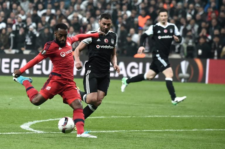 Lyon's Alexandre Lacazette (L) kicks the ball next to Besiktas' Dusko Tosic (C) during the UEFA Europa League second leg quarter final football match April 20, 2017