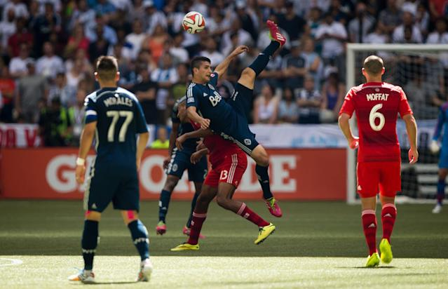 Vancouver Whitecaps' Johnny Leveron, centre, of Honduras, falls after getting his head on the ball in front of FC Dallas' Tesho Akindele (13) during the first half of an MLS soccer game in Vancouver, British Columbia, on Sunday July 27, 2014. (AP Photo/The Canadian Press, Darryl Dyck)
