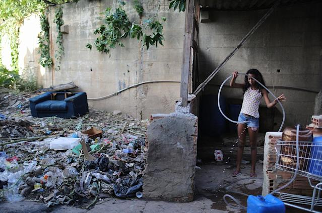 <p>A girl handles a hose while collecting water near her family's home in the Mangueira favela community in Rio de Janeiro, May 4, 2017. (Photo: Mario Tama/Getty Images) </p>