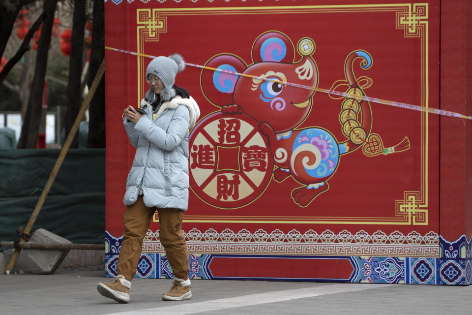 "A woman walks a depiction of a Rat with the words ""Bring in wealth and treasures"" ahead of the Chinese Lunar New Year Year of the Rat celebrations in Beijing on Thursday, Jan. 16, 2020. China's government welcomed an interim trade deal with Washington and said Thursday the two sides need to address each other's ""core concerns."" (AP Photo/Ng Han Guan)"