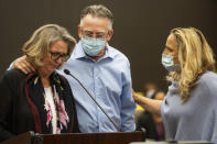 Gay Hardwick, left, is comforted by her spouse Bob Hardwick, center, and San Joaquin County's District Attorney Tori Verber Salazar during the second day of victim impact statements with Joseph James DeAngelo present at the Gordon D. Schaber Sacramento County Courthouse on Wednesday, Aug. 19, 2020, in Sacramento, Calif. Victims of the California serial killer and rapist, want him in a maximum security prison far, far away if he can't spend the rest of his life on death row. In June, DeAngelo pleaded guilty to 13 murders and 13 rape-related charges between 1975 and 1986. (Santiago Mejia//San Francisco Chronicle via AP, Pool)