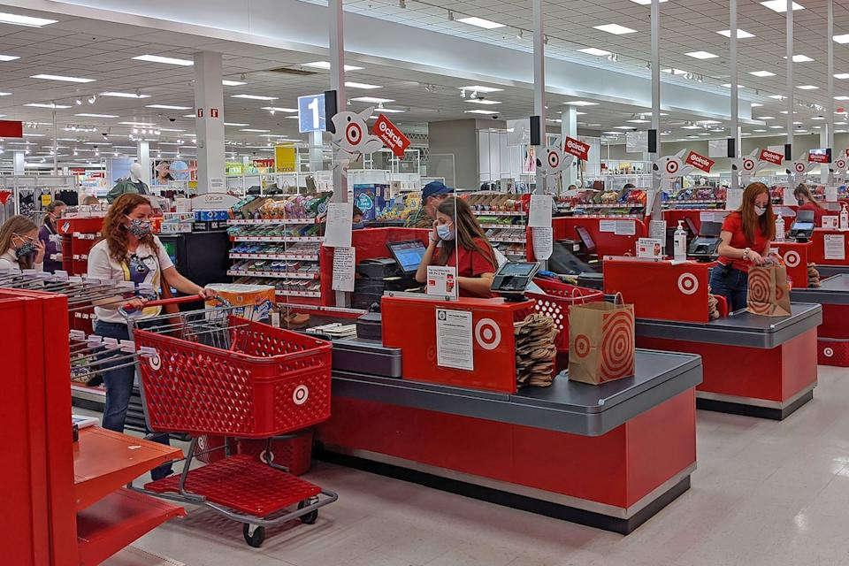 Target customers in checkout line wearing masks, separated from cashier by clear glass panel in Danvers Massachusetts in September 19, 2020