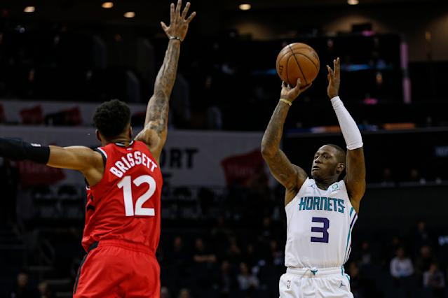 Charlotte Hornets guard Terry Rozier, right, shoots over Toronto Raptors forward Oshae Brissett during the first half of an NBA basketball game in Charlotte, N.C., Wednesday, Jan. 8, 2020. (AP Photo/Nell Redmond)