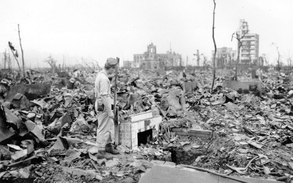 A man stands next to a tiled fireplace where a house once stood in Hiroshima - AP Photo/Stanley Troutman, Pool, File