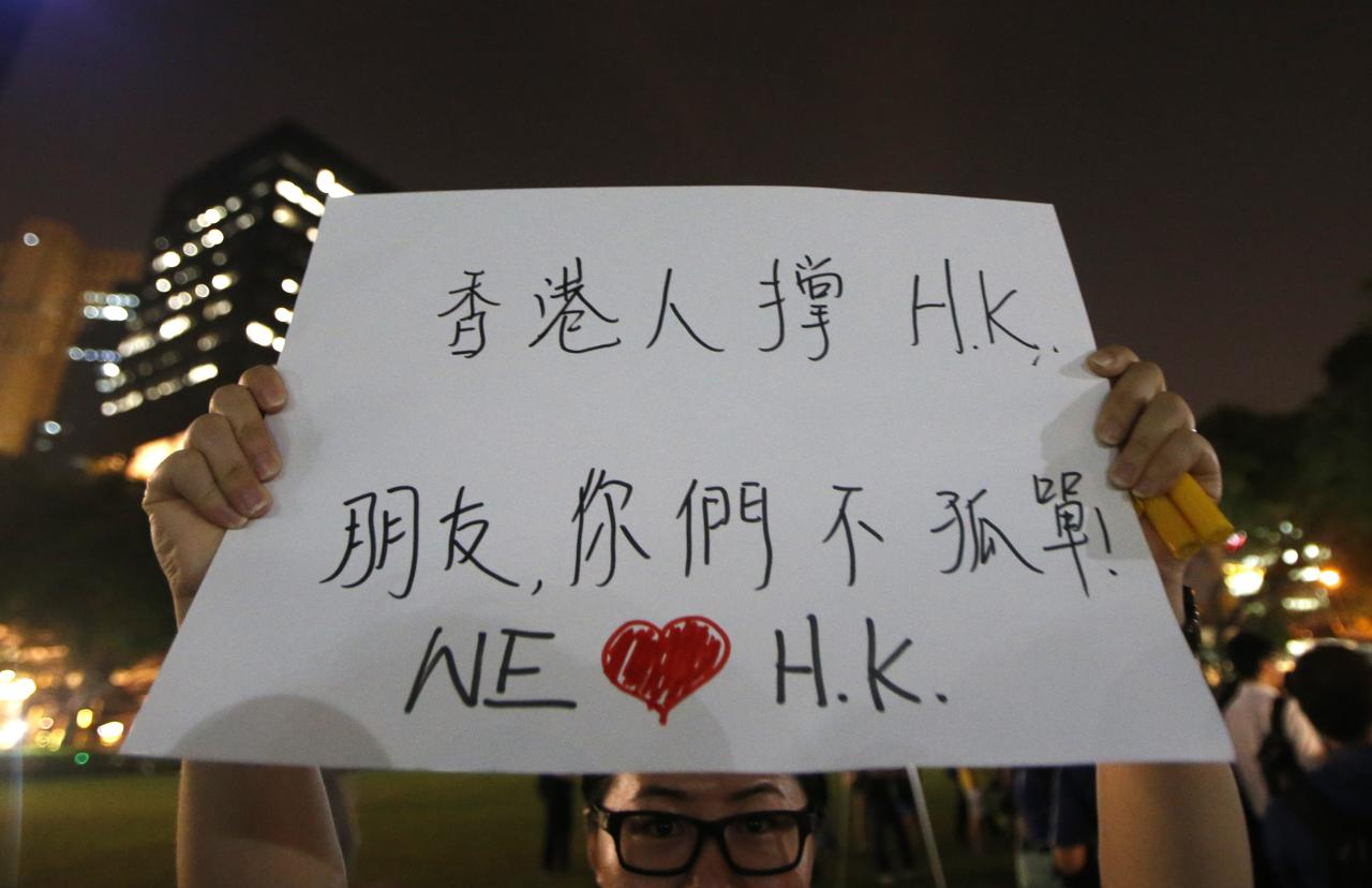 "A woman holds up a placard that reads, ""People of Hong Kong support Hong Kong. Friends, you are not alone""  during a candlelight vigil in solidarity with protesters of the ""Occupy Central"" movement in Hong Kong, at the Hong Lim Park Speakers' Corner in Singapore October 1, 2014. REUTERS/Edgar Su (SINGAPORE - Tags: POLITICS CIVIL UNREST)"