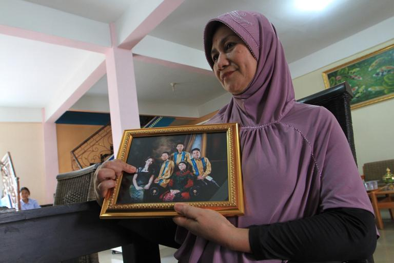 The mother of an Indonesian flight attendant who was travelling on AirAsia Flight QZ8501, points at her daughter on family photograph in Palembang, South Sumatra, on December 28, 2014