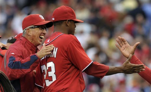 Washington Nationals manager Davey Johnson, left, congratulates his pitcher Edwin Jackson as they walk off the field after defeating the Cincinnati Reds 4-1 in a baseball game in Washington, Saturday, April 14, 2012. (AP Photo/Susan Walsh)