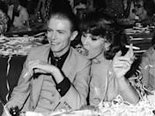 <p>Singer and actor David Bowie sits and holds a cigarette with Dutch actor Romy Haag at the club L'Alcazar in Paris, France.</p><p>Other celebrity visitors this year: comedian Jerry Lewis.</p>
