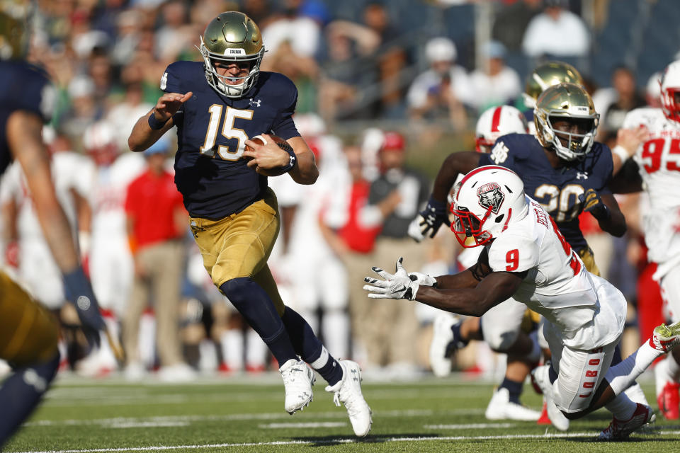 Notre Dame quarterback Phil Jurkovec (15) avoids New Mexico safety Jerrick Reed II (9) in the second half of an NCAA college football game in South Bend, Ind., Saturday, Sept. 14, 2019. (AP Photo/Paul Sancya)