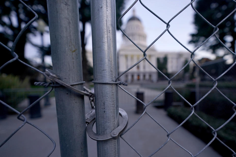 Handcuffs are used to secure two sections of temporary six-foot high chain link fence surrounding the state Capitol because of concerns over the potential for civil unrest, in Sacramento, Calif., Friday, Jan. 15 2021. With the FBI warning of potential violence at all state capitols Sunday, Jan. 17, the ornate halls of government and symbols of democracy looked more like heavily guarded U.S. embassies in war-torn countries. (AP Photo/Rich Pedroncelli)
