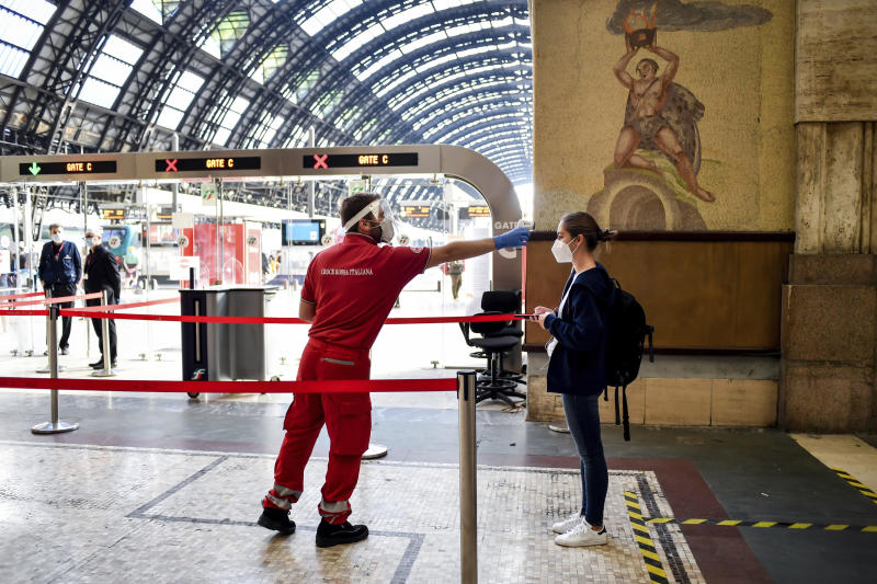 A passenger has her temperature taken to check for symptoms of COVID-19 before boarding a train to Milan's Central Station, Italy, Wednesday, June 3, 2020. A government-ordered ban on travel between regions ended on Wednesday. (Claudio Furlan/LaPresse via AP)