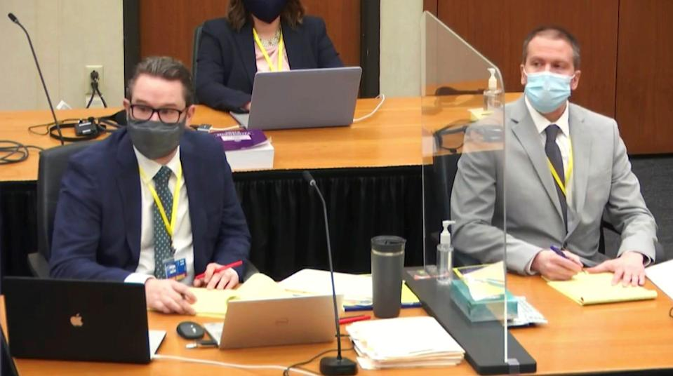 In this image from video, defense attorney Eric Nelson, left, and defendant former Minneapolis police Officer Derek Chauvin listen as Assistant Minnesota Attorney General Matthew Frank, questions witness Christopher Martin.