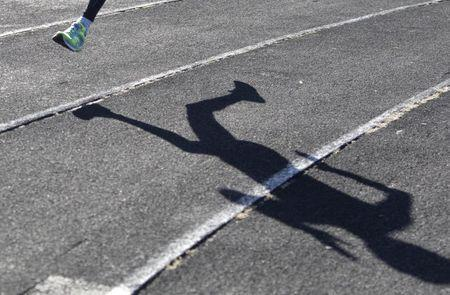 A sportsman casts a shadow on a race track while training at a local stadium in the southern city of Stavropol, Russia, November 10, 2015. REUTERS/Eduard Korniyenko