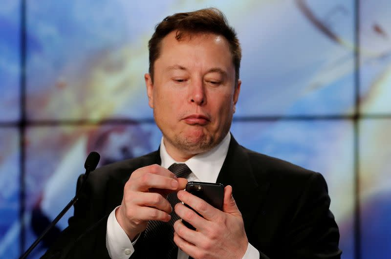 FILE PHOTO: SpaceX founder and chief engineer Elon Musk looks at his mobile phone during a post-launch news conference to discuss the SpaceX Crew Dragon astronaut capsule in-flight abort test at the Kennedy Space Center