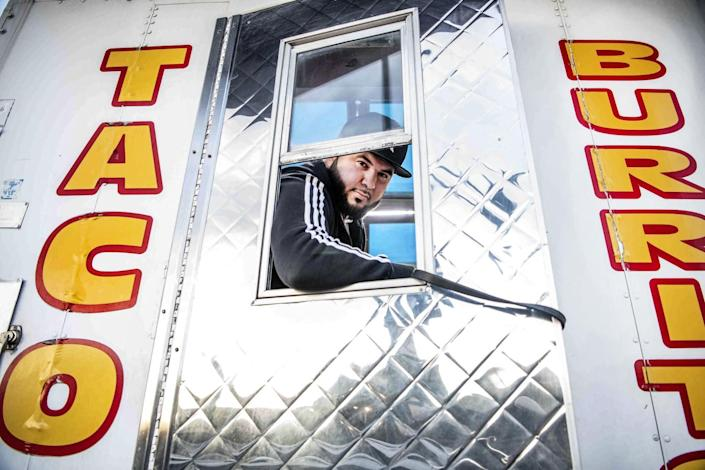 A man looks through the window of a door of a taco truck.