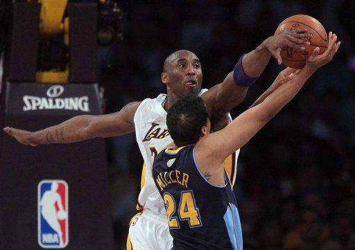 Kobe Bryant of the Los Angeles Lakers blocks a shot by Andre Miller of the Denver Nuggets