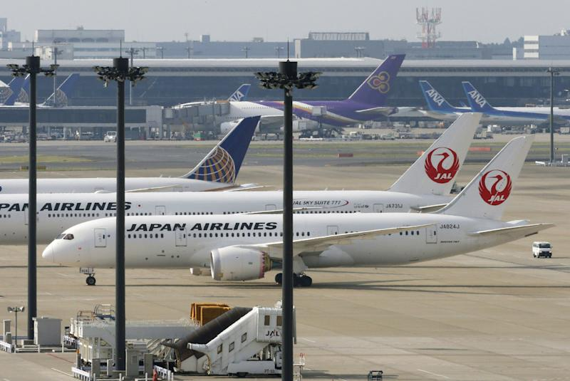 A Japan Airlines Boeing 787 plane, foreground, sits on a tarmac with others at Haneda Airport in Tokyo Friday, April 26, 2013. Japan's transport minister said Friday the government is poised to allow Japanese airlines to resume flying grounded Boeing 787s once they complete installation of systems to reduce fire risk in problematic lithium ion batteries. (AP Photo/Kyodo News) JAPAN OUT, MANDATORY CREDIT, NO SALES IN CHINA, HONG KONG, JAPAN, SOUTH KOREA AND FRANCE