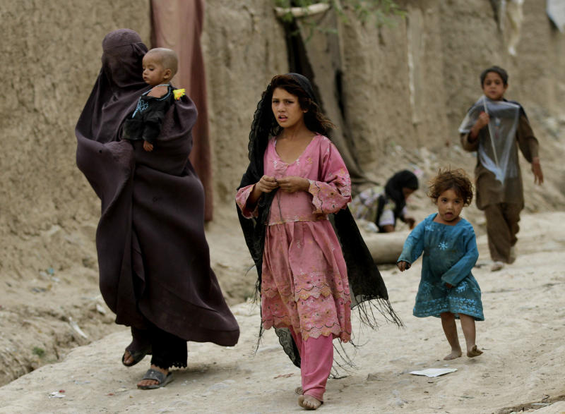 Displaced Afghans walks near their temporary homes on the outskirts of Kabul, Afghanistan, Tuesday, July, 30, 2013. (AP Photo/Ahmad Jamshid)