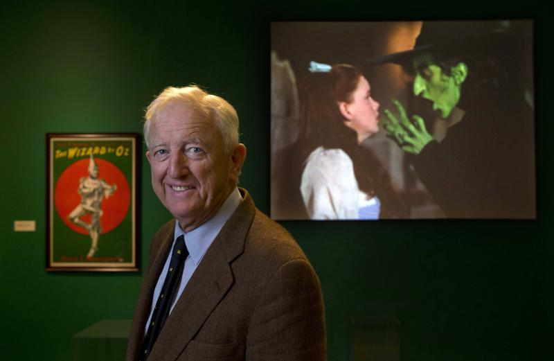 """In this Tuesday, Oct. 8, 2013 photo, Ham Meserve, of Southport, Maine, the son of actress Margaret Hamilton, poses at the Farnsworth Museum, in Rockland, Maine. Hamilton is seen on the screen at right playing the role of the wicked witch of the West in the movie, """"The Wizard of Oz."""" The world's largest collection of materials from the movie is being exhibited a few months after the release of a prequel to the original film and the release of the original movie in I-Max format. (AP Photo/Robert F. Bukaty)"""