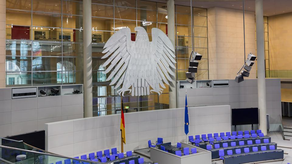 Berlin, Germany - Jan 9, 2020: View on interior of the empty plenary hall of the German Federal Parliament (Deutscher Bundestag). In the middle the german coat of arms (eagle, so-called Bundesadler). Originally built by Paul Wallot, redesigned by Sir Norman Foster. Re-opened in 1999.