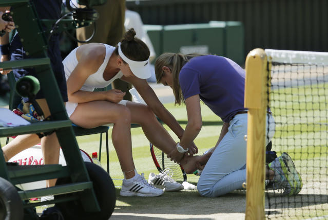Simona Halep of Romania receives treatment on her ankle during the women's singles semifinal match against Eugenie Bouchard of Canada at the All England Lawn Tennis Championships in Wimbledon, London, Thursday, July 3, 2014. (AP Photo/Ben Curtis)