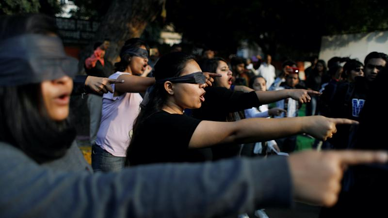 Protestors wearing blindfolds take part in a protest in India