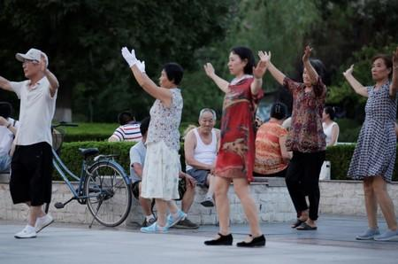 An elderly man rests as residents dance during their daily exercise at a city square in Weifang