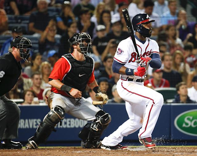Atlanta Braves right fielder Jason Heyward, right, drives in a run with a single as Miami Marlins catcher Jarrod Saltalamacchia, left, looks on in the seventh inning of a baseball game Monday, April 21, 2014 in Atlanta. (AP Photo/John Bazemore)