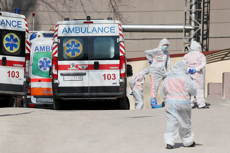 FILE PHOTO: Medical personnel stand next to ambulances with COVID-19 patients in Kyiv