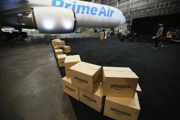 A line of Amazon boxes getting loaded onto an Amazon cargo plane.