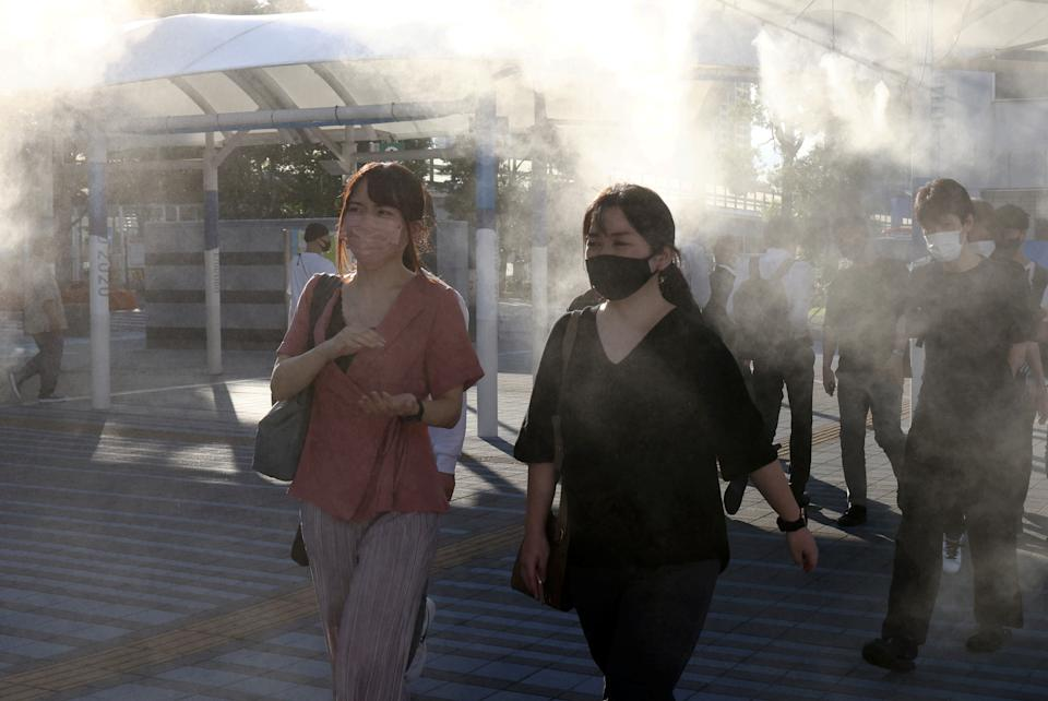 TOKYO, JAPAN  JULY 16, 2021: Locals stand at a bus stop spraying air cooling mist. Valery Sharifulin/TASS (Photo by Valery Sharifulin\TASS via Getty Images)