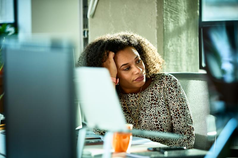 Close up view of mid adult businesswoman in animal print blouse, resting head on hand in office, introspection, daydreaming, distraction, pensive