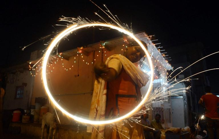 A minority Pakistani Hindu reveller waves sparklers on the occasion of Diwali in Karachi on November 13, 2012. Diwali, the festival of lights, is celebrated with jubilation and enhusiasm as one of the biggest Hindu festivals. People decorate their homes with flowers and Diyas (earthen lamps), celebrate the homecoming of the God Ram after vanquishing the demon king Ravana and honour the Hindu goddess of wealth, Lakshmi. AFP PHOTO/Asif HASSAN