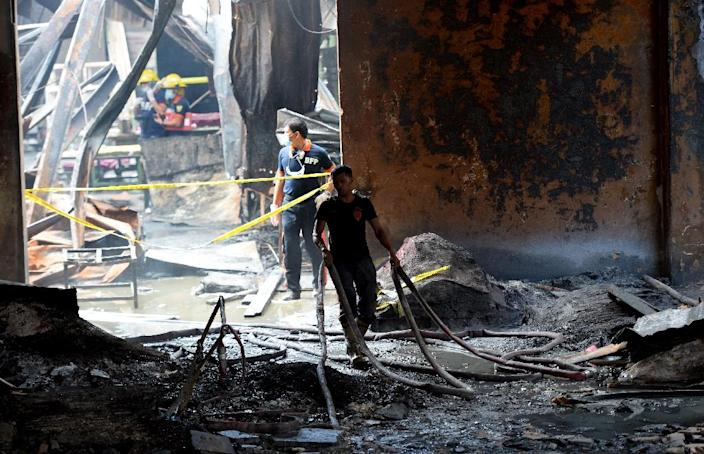 Fire investigators look for evidence amongst the ruins of a footwear factory in suburban Manila on May 14, 2015, a day after it was gutted by fire (AFP Photo/Ted Aljibe)