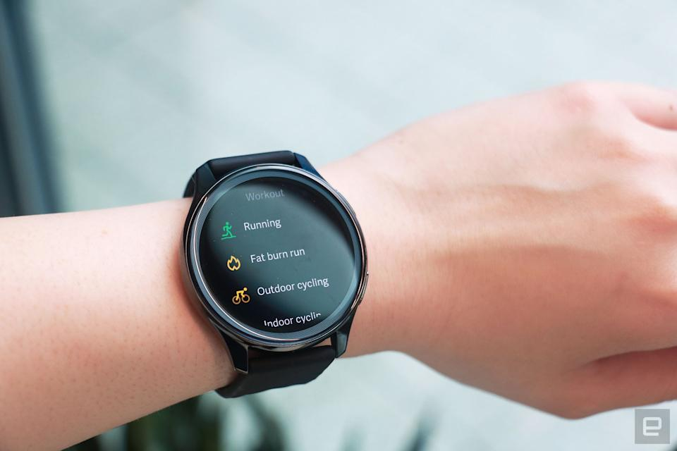 OnePlus Watch review photos. OnePlus Watch on a wrist showing a list of workouts including Running, Fat Burn Run, Outdoor cycling and Indoor cycling.