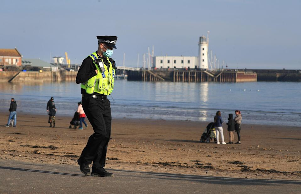 <p>A police officer patrols a  Scarborough beach to turn away sunbathers ignoring the Governments Stay At Home message</p> (PA)