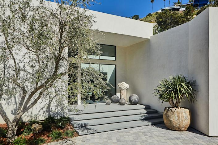 """<div class=""""caption""""> At the entrance of the house, the 18th-century French marble bust of Royal Commander was placed on a cut concrete stand from <a href=""""http://www.cachecollection.com/browse.cfm"""" rel=""""nofollow noopener"""" target=""""_blank"""" data-ylk=""""slk:Caché"""" class=""""link rapid-noclick-resp"""">Caché</a> surrounded by gray stone spheres on the floor (from unknown source). The stone urn planter is from <a href=""""https://www.bdantiques.com/"""" rel=""""nofollow noopener"""" target=""""_blank"""" data-ylk=""""slk:Big Daddy's Antiques"""" class=""""link rapid-noclick-resp"""">Big Daddy's Antiques</a>. </div>"""