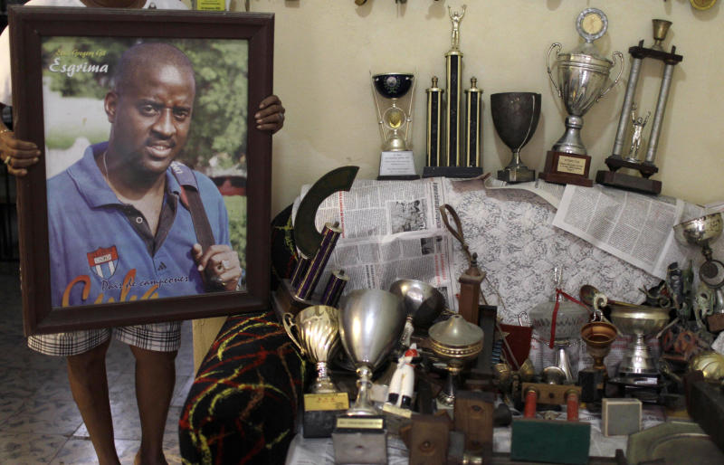Maria Victoria Gil, mother of swordsman Elvis Gregory, shows a framed photo of her son next to a trove of trophies awarded to her son, at her home, in Havana, Cuba, Friday, Nov. 16, 2012. Gregory, an Olympic silver medalist, who defected from the Cuban team at a tournament in Lisbon in 2002, hopes to return to Cuba next year so he can finally meet his only child, a 10-year-old girl who was only 15 days old when he abandoned his country. New migratory laws have now made it possible for high-profile defectors once considered deserters or traitors to return to the homeland they abandoned. The new rules could potentially affect many leading cultural and athletic figures, from musicians and doctors to ballet dancers. (AP Photo/Franklin Reyes)