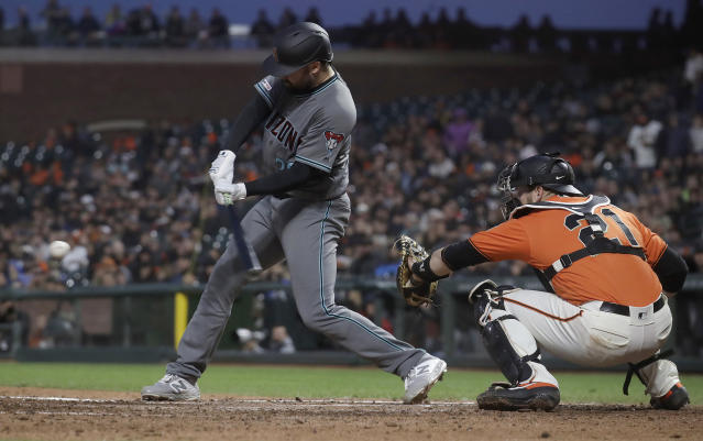 Arizona Diamondbacks' Robbie Ray hits a two-run single in front of San Francisco Giants catcher Stephen Vogt during the third inning of a baseball game in San Francisco, Friday, May 24, 2019. (AP Photo/Jeff Chiu)