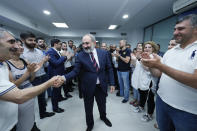 Armenian acting Prime Minister Nikol Pashinyan greets his party colleagues after parliamentary elections in Yerevan, Armenia, Monday, June 21, 2021. Results released Monday showed the party of Pashinyan won the snap parliamentary elections he called to ease anger over a peace deal he signed with Azerbaijan. (Tigran Mehrabyan/PAN Photo via AP)