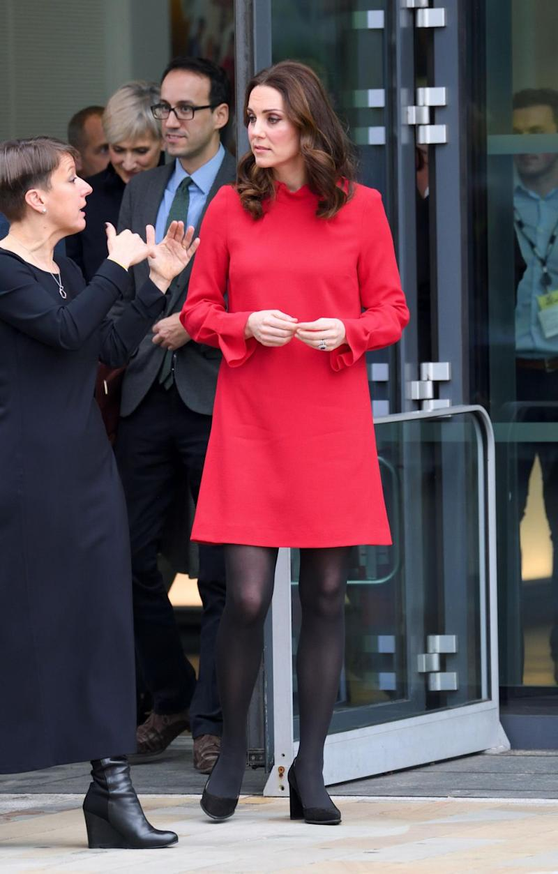 Underneath the coat she has a stunning red Goat dress on. Photo: Getty Images