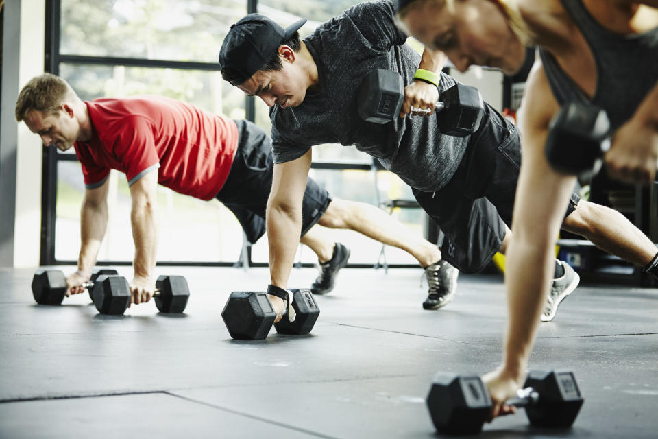 Group of friends doing pushups with dumbbells in gym gym