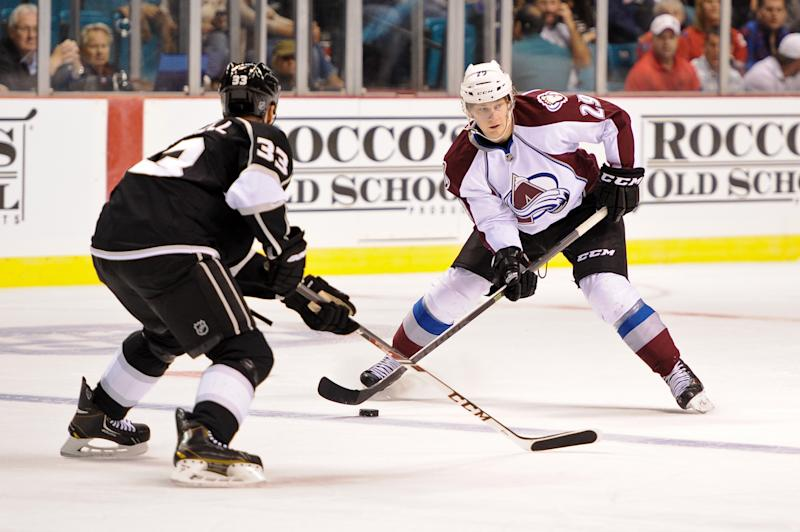Colorado Avalanche center Nathan MacKinnon (29) looks to pass the puck in front of Los Angeles Kings defenseman Willie Mitchell (33) in the first period of an NHL preseason hockey game on Saturday, Sept. 28, 2013 in Las Vegas. (AP Photo/David Cleveland)