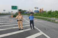 Policemen guard behind barricades set up to control the traffic in Hanoi, Vietnam, Saturday, July 24, 2021. Vietnam announced a 15-day lockdown in the capital Hanoi starting Saturday as a coronavirus surge spread from the southern Mekong Delta region. (AP Photo/Hieu Dinh)
