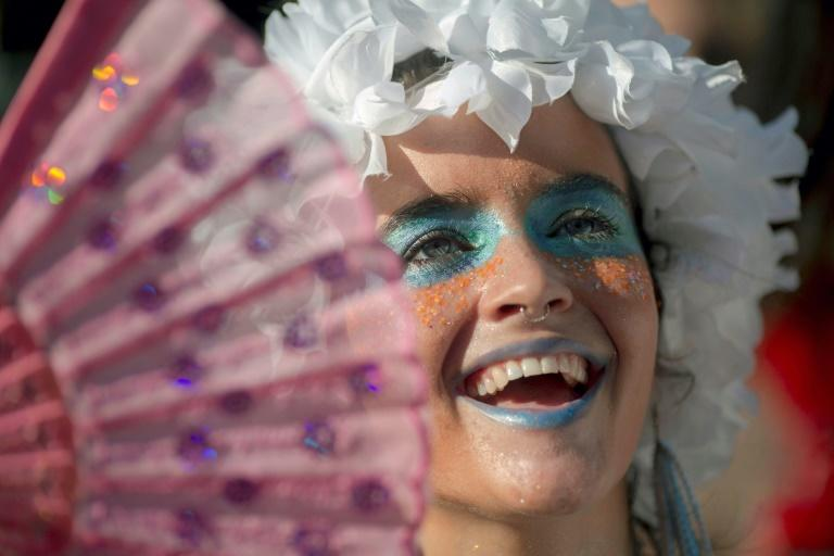 "A member of the ""Ceu Na Terra"" (Heaven on Earth) group dances in a street party a week ahead of the main carnival event in Rio de Janeiro"