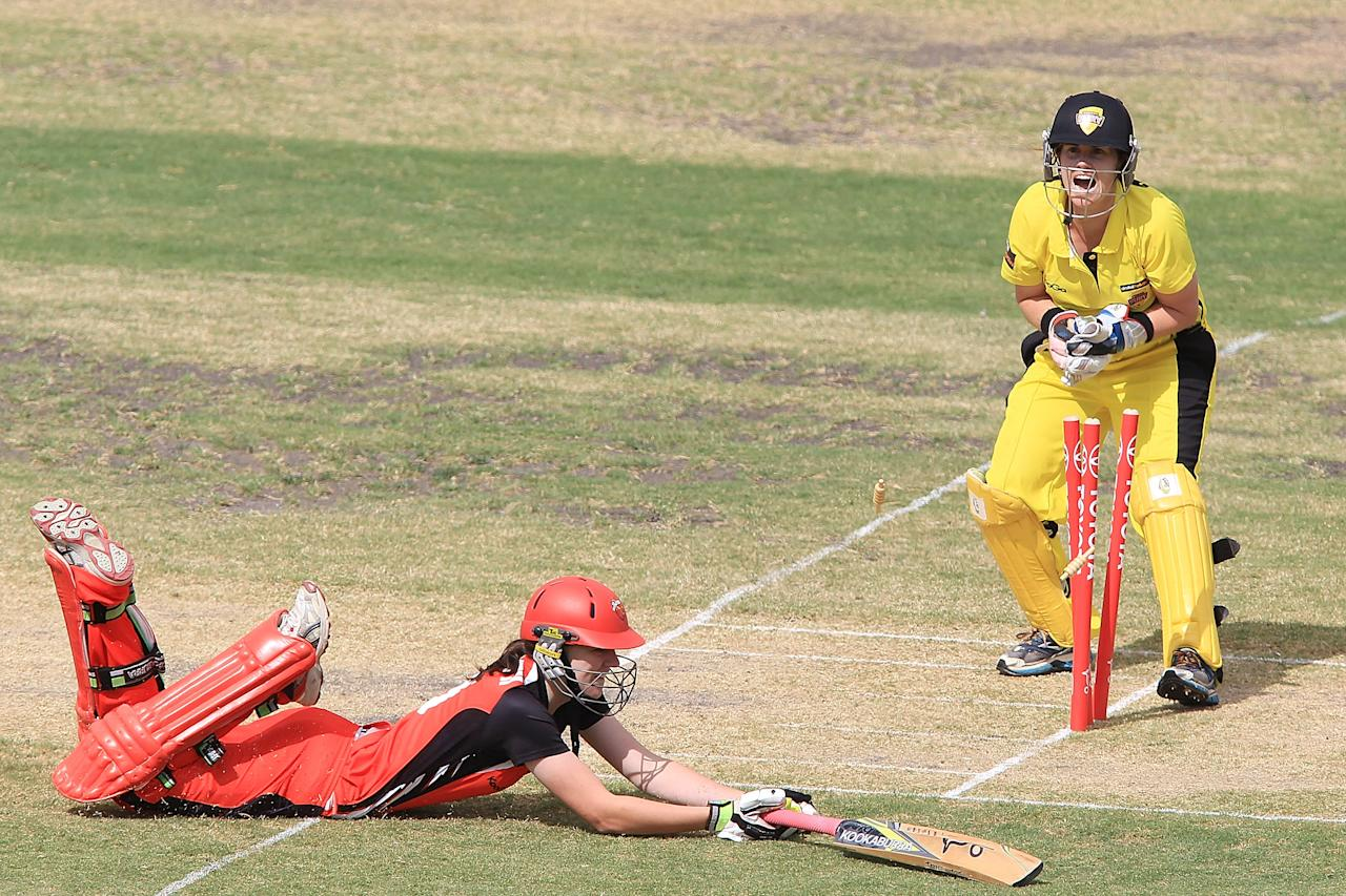 ADELAIDE, AUSTRALIA - NOVEMBER 08: Jenny Wallace of the Fury appeals for a run-out as Tahlia McGrath of the Scorpions makes her ground during the WT20 match between South Australia and Western Australia on November 8, 2013 in Adelaide, Australia.  (Photo by Morne de Klerk/Getty Images)