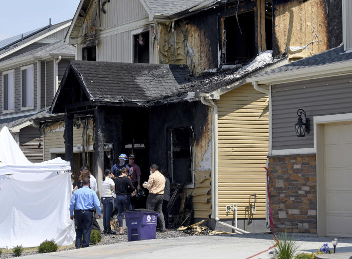 Investigators stand outside a house where five people were found dead after a fire in suburban Denver, Wednesday, Aug. 5, 2020. Three people escaped the fire by jumping from the home's second floor. Investigators believe the victims were a toddler, an older child and three adults. Authorities suspect was intentionally set. (AP Photo/Thomas Peipert)